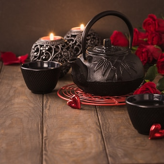 Valentine's day composition with green tea, black teapot, candles and roses on wooden table. valentines day greeting card concept with copy space Premium Photo