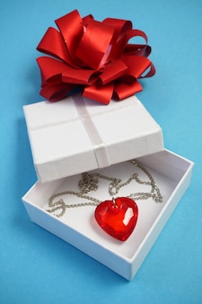 Valentine's day composition with red pendant heart in present box on blue background
