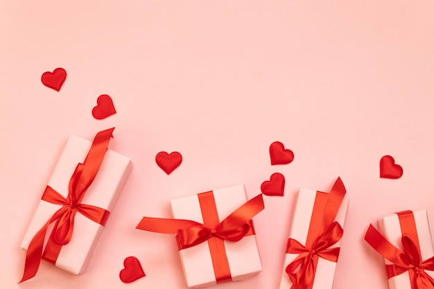 Valentine's day composition with surprise gifts with red bow and heart shape on a pink background with copyspace