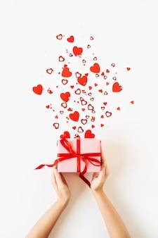 ピンクのギフトボックスと白い表面にハートのシンボルの紙吹雪を保持している女性の手でバレンタインデーの構成