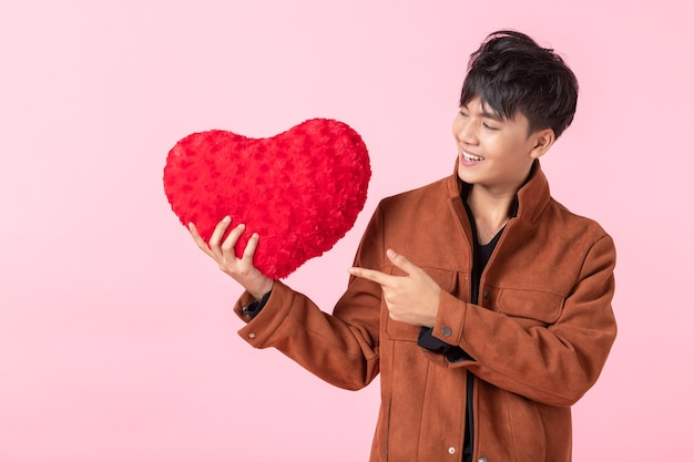 발렌타인 데이 컨셉인 아시아인은 분홍색 빈 카피 공간 스튜디오 배경에서 격리된 사랑에 빨간 하트 모양의 베개를 들고 있는 잘생긴 청년입니다.