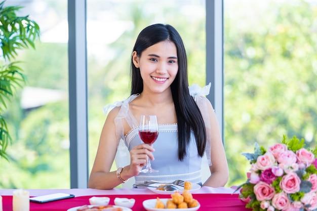 발렌타인 데이 컨셉으로, 아시아 어린 소녀는 와인잔과 붉은 장미와 분홍색 장미 꽃다발을 들고 식탁에 앉아 레스토랑 배경에서 그녀의 남자를 기다리고 있습니다.