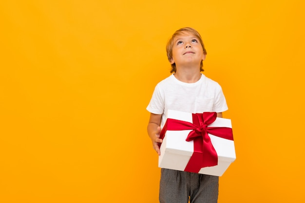 Valentine's day concept. attractive boy with gift box on bright yellow background