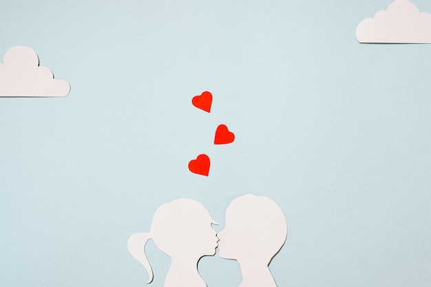 Valentine's day concept. cardboard silhouettes girl and boy kissing. creative love card. red hearts, clouds on a pastel blue background. flat lay, top view.