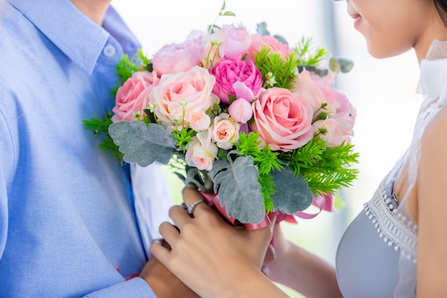 Valentine's day concept,close up of asian young happy sweet couple holding bouquet of red and pink roses after lunch in a restaurant