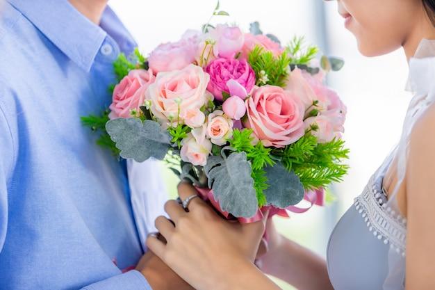 День святого валентина концепция, крупный план азиатских молодые счастливые сладкие пары, держа букет из красных и розовых роз после обеда в ресторане