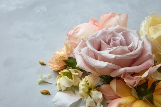 발렌타인 데이 개념입니다. 회색 배경에 표시되는 복사 공간이 있는 큰 장미의 근접 촬영입니다. 다양한 종류의 꽃들 사이에서 장미.