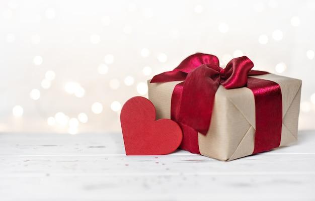 Концепция дня святого валентина. подарочная коробка с красной лентой и формой сердца на красном фоне боке. открытка, баннер, пространство копу