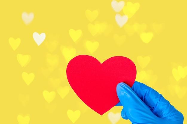 Концепция дня святого валентина. рука в медицинских синих перчатках держит форму красного сердца