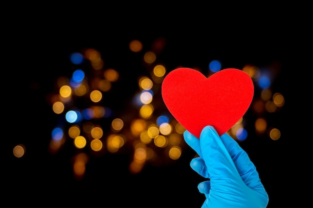 Valentine's day concept. a hand in medical blue gloves holds a red heart shape