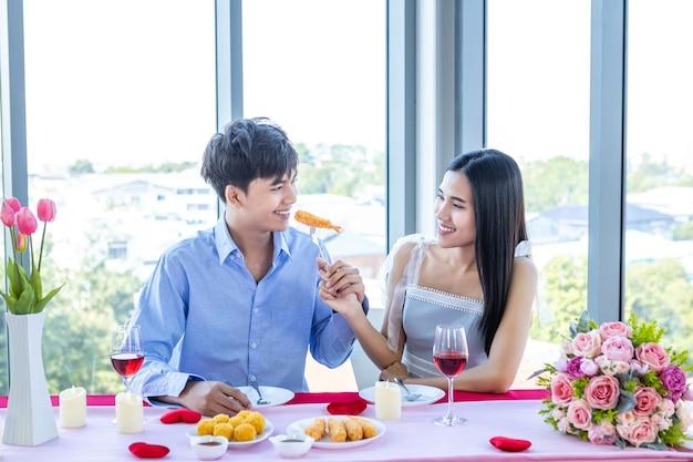 バレンタインデーのコンセプト、レストランの背景にバラの花束とロマンチックなランチを持っている幸せなアジアの若い甘いカップル。