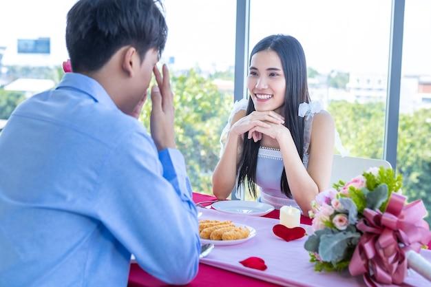 발렌타인 데이 컨셉인 해피 아시안 젊은 커플은 레스토랑 배경에서 장미 꽃다발과 함께 낭만적인 점심을 먹고 있습니다.