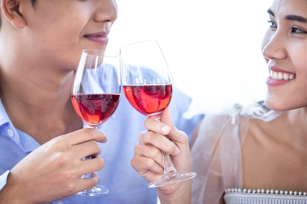 バレンタインデーのコンセプト、レストランの背景でトーストワイングラスをチリンと鳴らしながらロマンチックなランチを持っている幸せなアジアの若い甘いカップル。