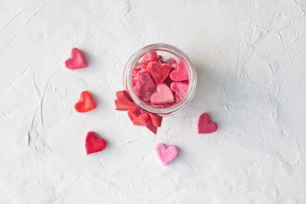 Valentine's day concept. jar with hearts of sweets on a light background, top view