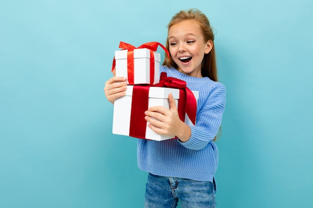 Valentine's day concept. little girl barely holds two gifts on a light blue