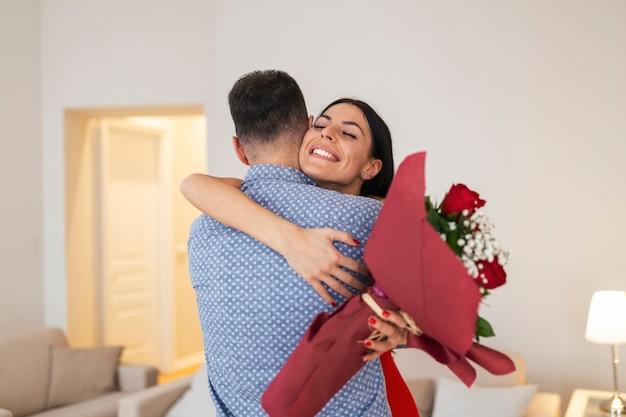 Концепция дня святого валентина. влюбленные обнимают друг друга. красивый мужчина удивляет свою девушку красными розами дома