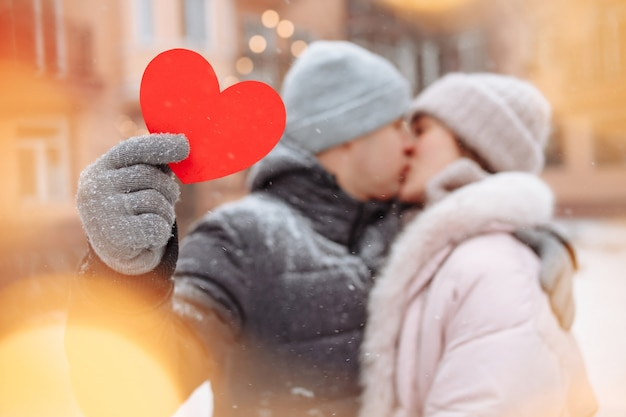 Valentine's day concept, loving couple kiss and hug at a winter snowy park. young man holds a red paper heart while celebrating all lovers day with his girlfriend. a couple feeling warm together.