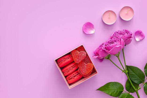 발렌타인 데이 개념. 마멀레이드와 마카롱이있는 분홍색 상자와 분홍색 테이블에 아름다운 장미