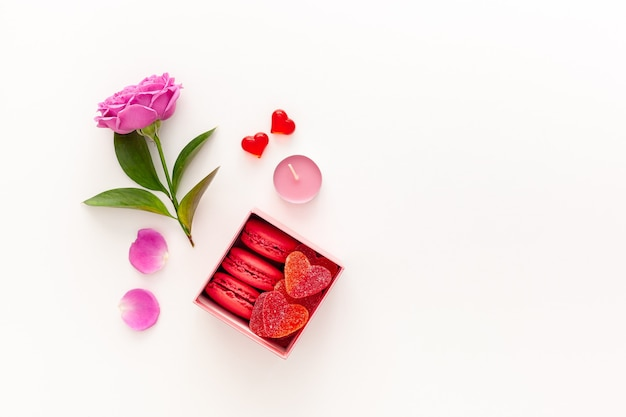 Valentine's day concept. pink box with marmalade and macaroons and a beautiful rose on a pink table