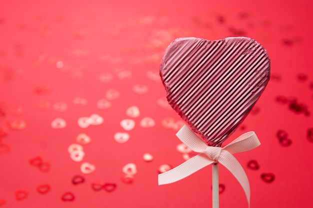 Valentine's day concept, pink lollipop in the shape of heart isolated on red background, with confetti bokeh, copy space.