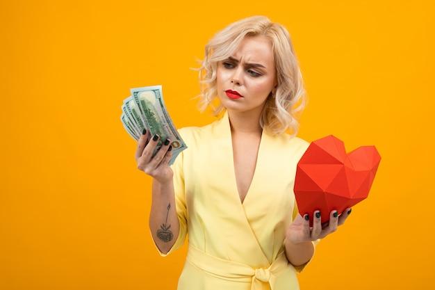 バレンタインデーのコンセプトです。黄色の手で紙とドル札で作られた赤いハートと赤い唇を持つ少女の肖像画