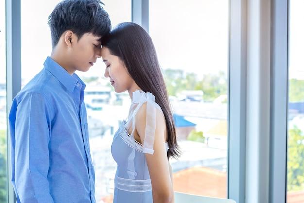 バレンタインデーのコンセプト、アジアの若い幸せなカップルの肖像画自宅でのキスの顔の背景、コピースペース、ラブストーリーカップル