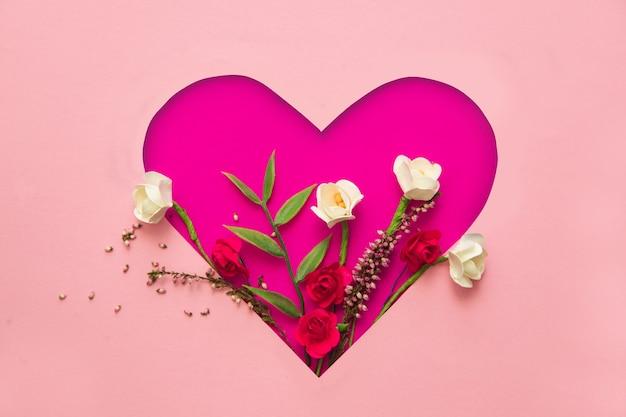 バレンタインデーのコンセプト。すべての愛好家の休日のためのポストカード。紙と花でできたハート。