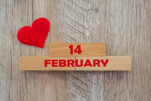 Концепция дня святого валентина. красное сердце и надпись «14 февраля» на деревянных блоках.