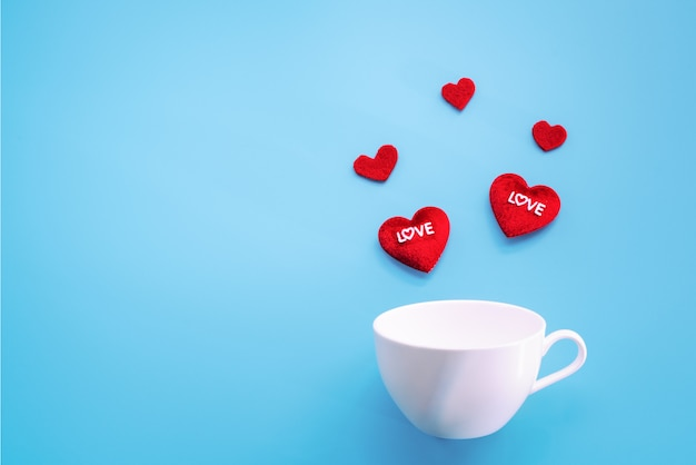 Valentine's day concept. red heart with white coffee cup on blue background