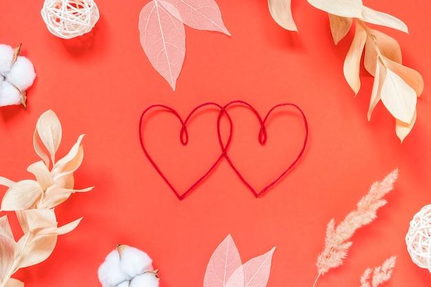 День святого валентина концепция красные сердца и различные сушеные цветы на красном фоне