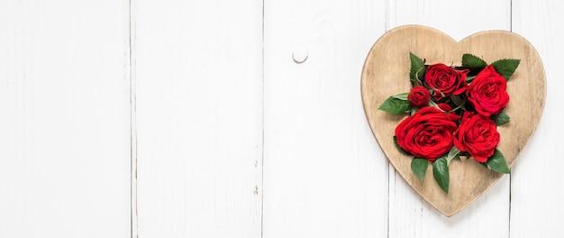 День святого валентина концепция красные розы и деревянное сердце на белом фоне