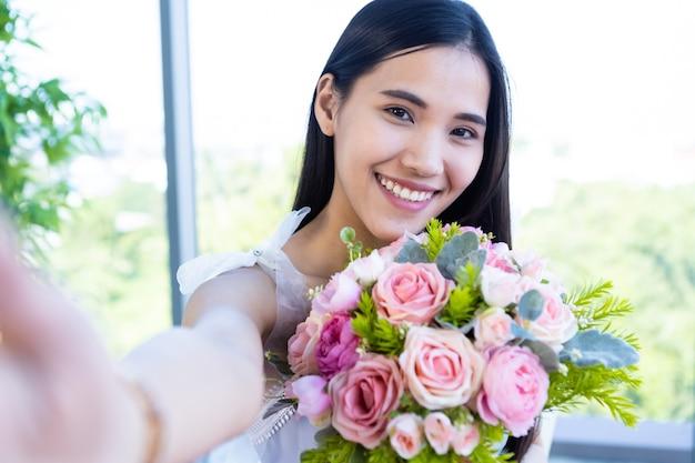 Концепция дня святого валентина, селфи счастливой улыбающейся азиатской молодой женщины, сидящей за столом, держащей букет роз на фоне ресторана