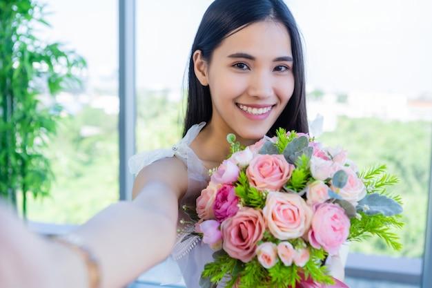 バレンタインのコンセプト、レストランでバラの花束を持ってテーブルフードに座っているアジアの若い女性を笑顔の幸せのselfie