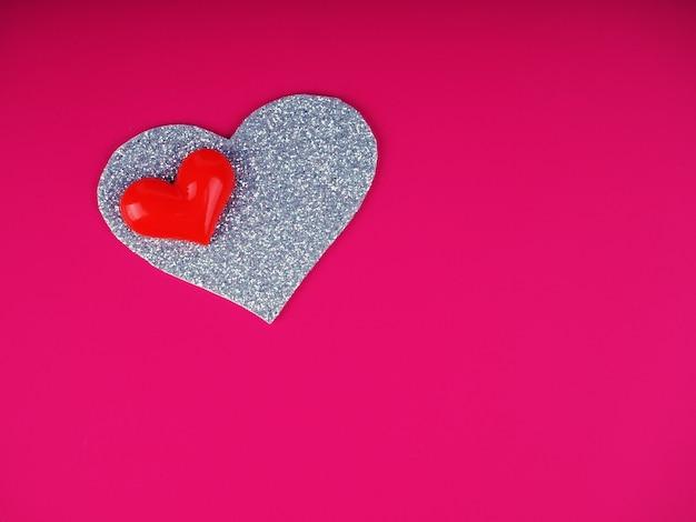 バレンタインデーのコンセプト、ピンクの背景にシルバーと赤のハート、グリーティングカード。