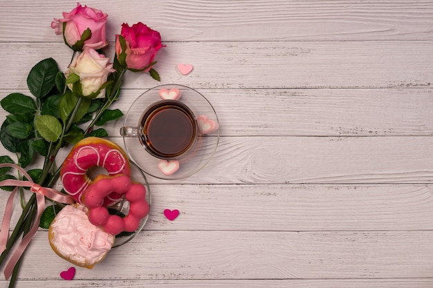 Valentine's day concept. tea cup, donuts, gifts and roses on wooden table