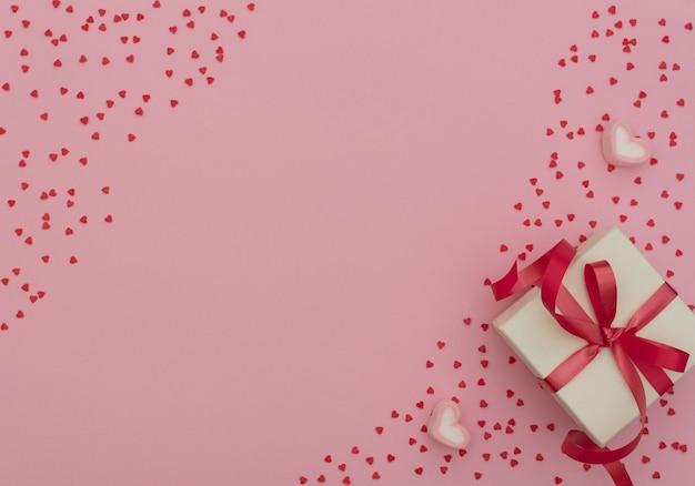 Концепция дня святого валентина. белая подарочная коробка с красной лентой и двумя зефирами в форме сердца на розовом фоне с множеством маленьких красных сердечек. валентинка. плоский стиль с копией пространства.