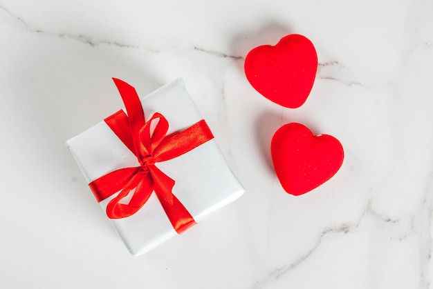 Valentine's day concept, white wrapped gift box with red ribbon and red velvet hearts, on white marble background, copy space top view
