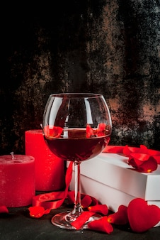 Valentine's day concept, white wrapped gift box with red ribbon, rose flower petals, red wine glass, with red candle, on dark stone background, copy space