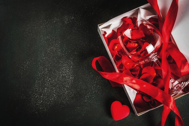 Valentine's day concept, white wrapped gift box with red ribbon, with rose flower petals in wine glass, with red candle, on dark stone background, copy space top view