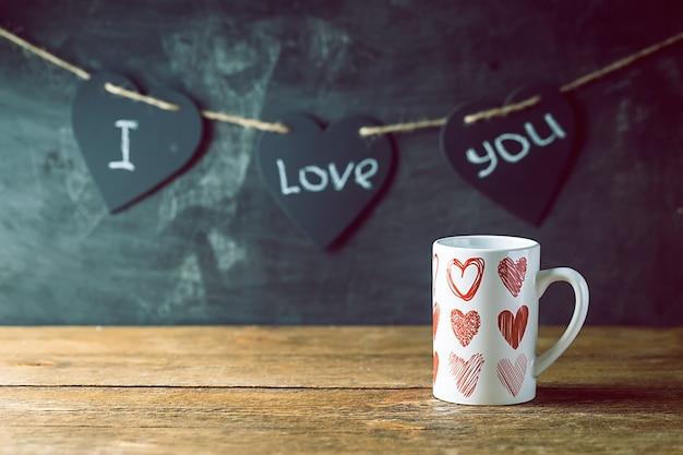 칠판 배경 위에 뜨거운 음료 한잔과 함께 발렌타인 개념