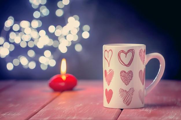 빛나는 배경 위에 뜨거운 음료 한잔과 함께 발렌타인 개념