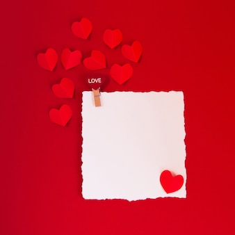 Valentine's day concept with red hearts on red background and white card for text,  flat lay, copy space