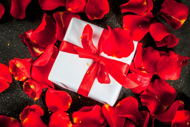 Valentine's day concept, with rose flower petals and white wrapped gift box with red ribbon, on dark stone background, copy space top view