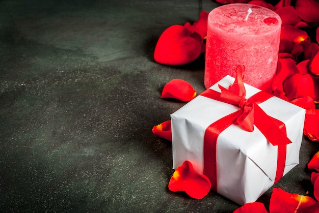 Valentine's day concept, with rose flower petals and white wrapped gift box with red ribbon, on dark stone background, copy space