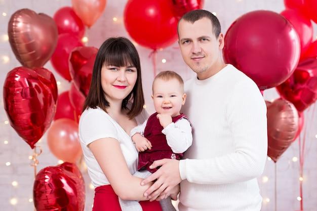 Концепция дня святого валентина - молодая семья с маленькой дочерью на фоне красных воздушных шаров в форме сердца