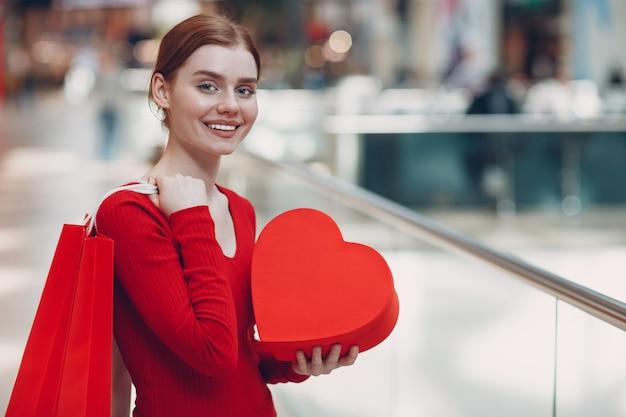 Концепция дня святого валентина. молодая женщина с хозяйственной сумкой и портретом подарочной коробки в форме красного сердца в торговом центре