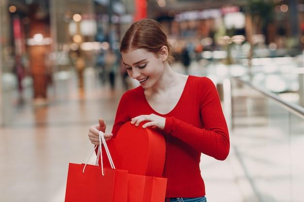 Концепция дня святого валентина. молодая женщина с хозяйственными сумками и портретом коробки в форме красного сердца в торговом центре