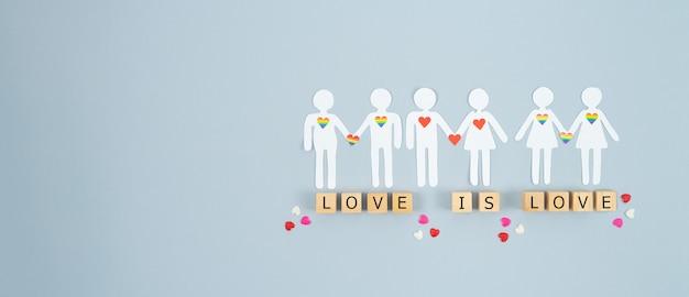 バレンタイン・デー。異なるジャンルのカップルが木製のブロックにloveisloveの文字で紙から切り出されています。コピースペース