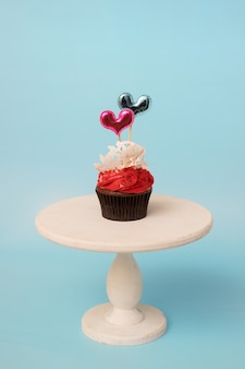 Valentine's day cupcake with sugar lace and hearts on white wooden stand