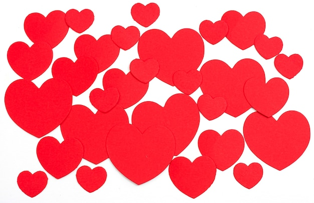 バレンタインデーは、白い背景で赤い紙のハートをカットしました。